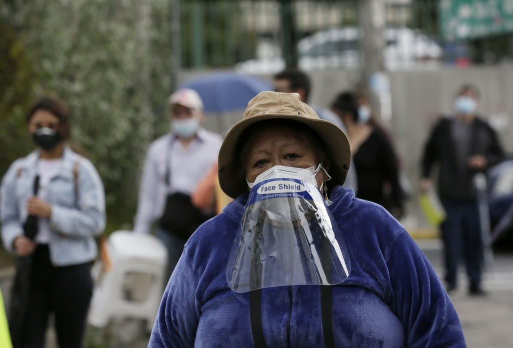 A woman with a face shield worn over her mask joins retirees in long lines waiting to be vaccinated against COVID-19, outside a vaccination center of ...