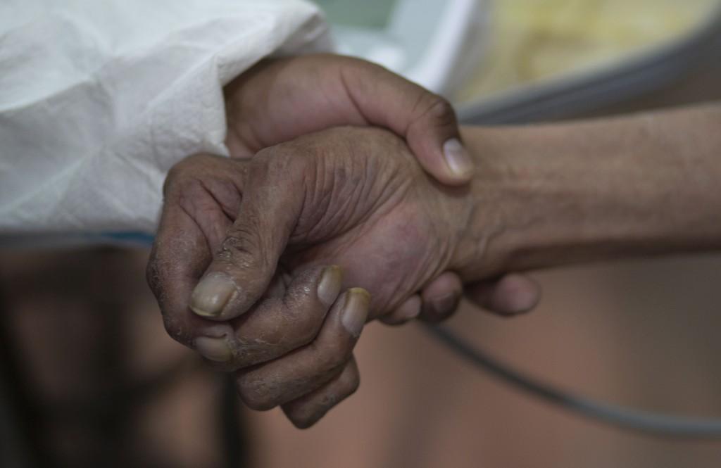 A health worker takes a man's pulse after giving him a shot of the Sputnik V COVID-19 vaccine at the Universidad Publica de El Alto, during a vaccinat...