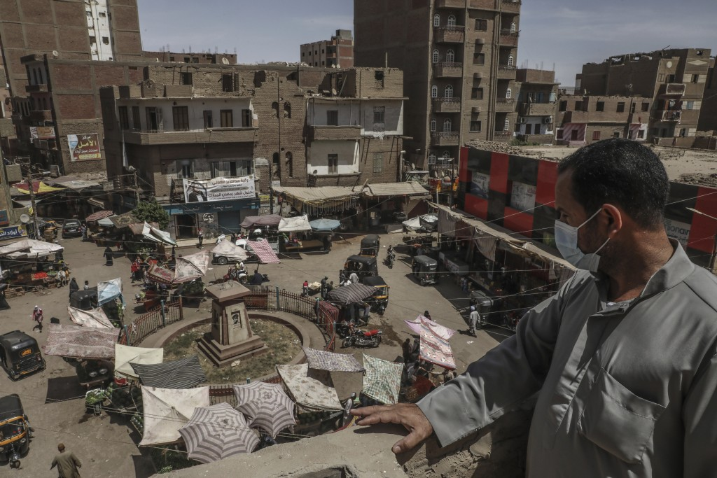 Ashraf Sayed a resident of the town of Monshah, where a surge in coronavirus pandemic cases is taking place, looks at a market on the top of a residen...