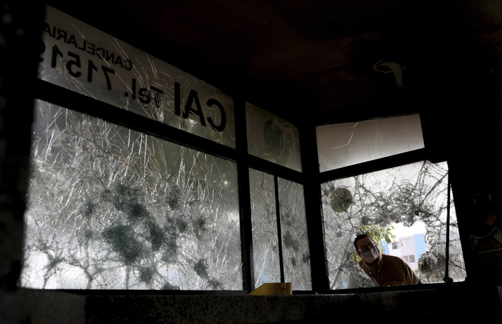 A man looks into a police post damaged by protesters the previous night in Bogota, Colombia, Wednesday, May 5, 2021. Protests that began last week ove...