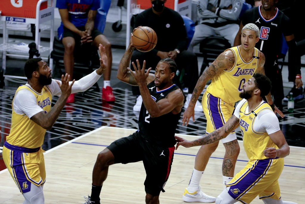 Los Angeles Clippers' Kawhi Leonard looks to pass the ball while defended by Los Angeles Lakers' Andre Drummond, left, Anthony Davis, right, and Kyle ...