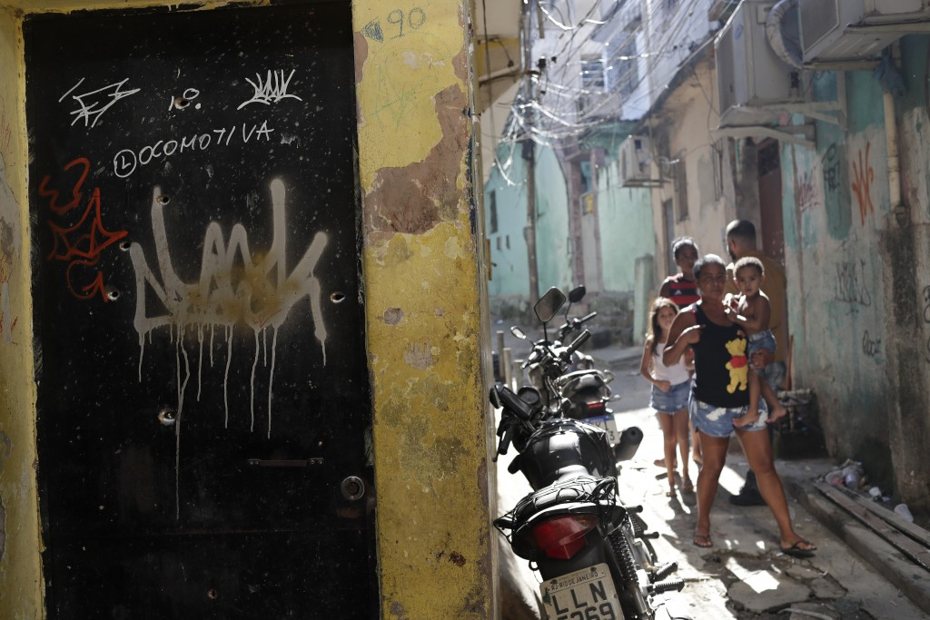 Residents walk near a doorway scared with bullet holes after a police raid against alleged drug traffickers in Rio de Janeiro, Brazil, Thursday, May 6...