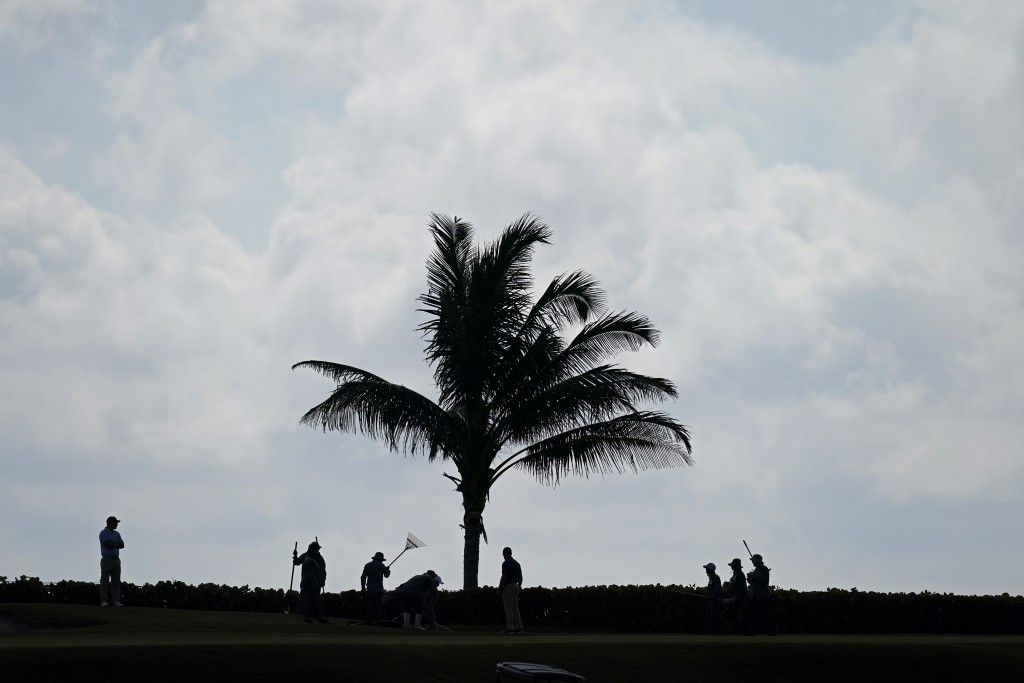 Workers groom the course after heavy thunderstorms moved through yesterday, on a practice day for the Walker Cup golf tournament at Seminole Golf Club...