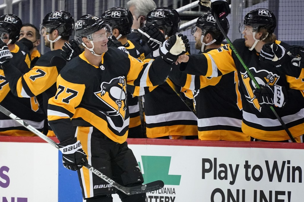 Pittsburgh Penguins' Jeff Carter (77) returns to the bench after scoring his third goal of the game during the second period of an NHL hockey game aga...