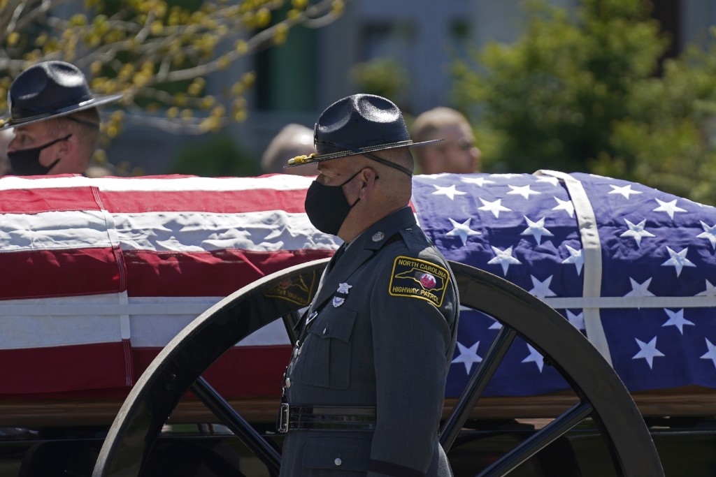 A caisson approaches the Holmes Convocational Center for the funeral services of Watauga County Sheriff's Deputies Sgt. Chris Ward and K-9 Deputy Loga...