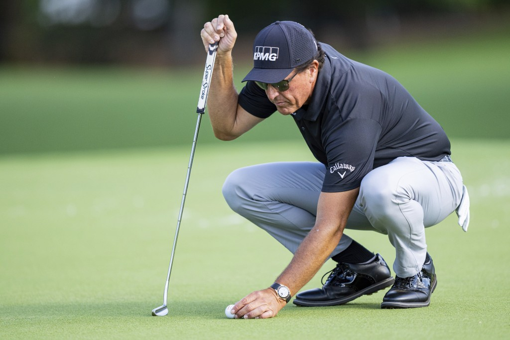 Phil Mickelson lines up his putt on the ninth hole during the first round of the Wells Fargo Championship golf tournament at Quail Hollow Club on Thur...