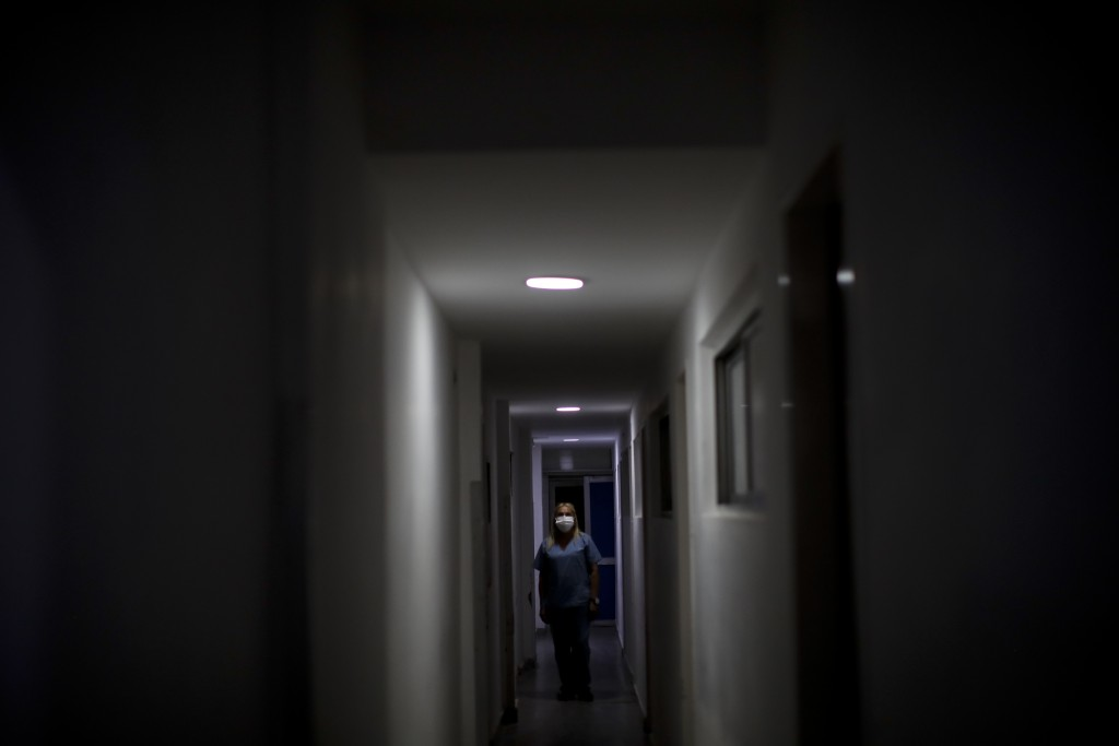 Nurse Lidia Del Valle walks inside the San Andres Clinic which has been occupied by its former workers since it closed at the start of the year follow...