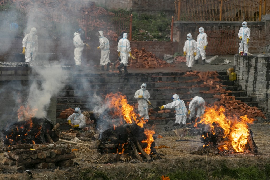 FILE - In this May 5, 2021, file photo, Nepalese men in personal protective suits cremate the bodies of COVID-19 victims while others extend the crema...