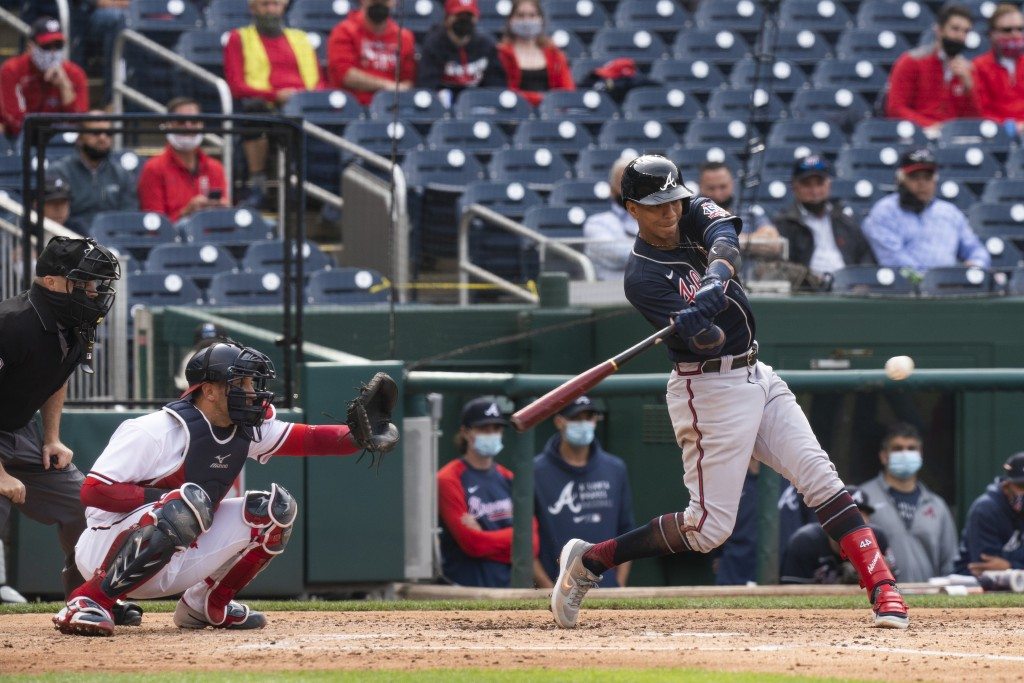 Atlanta Braves' Ehire Adrianza, hits a two-run single during the fourth inning of a baseball game against the Washington Nationals in Washington, Thur...