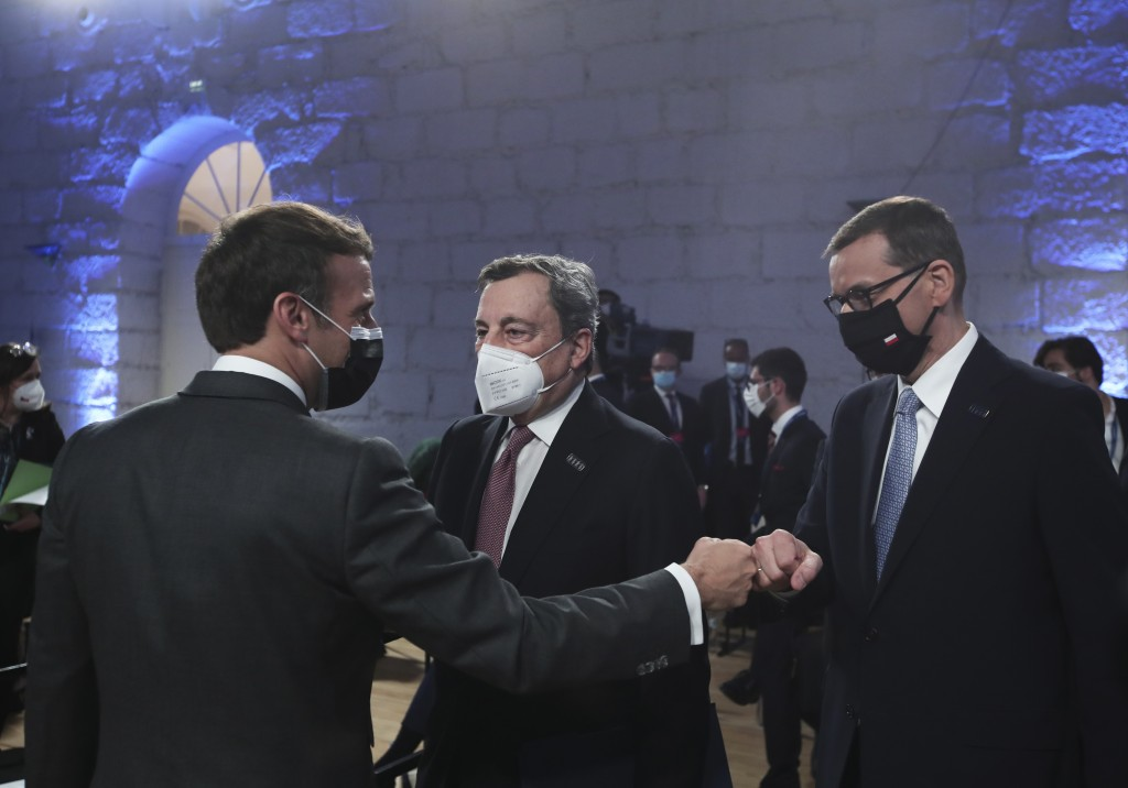 French President Emmanuel Macron, left, fist bumps Poland's Prime Minister Mateusz Morawiecki during the opening ceremony of an EU summit at the Alfan...