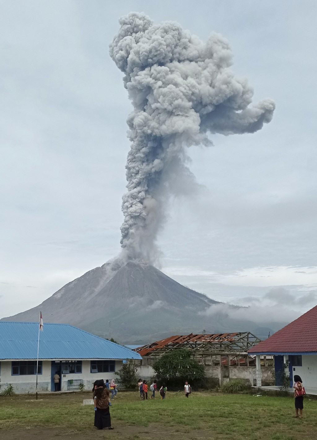 Mount Sinabung releases volcanic materials during an eruption as seen from a school yard in Karo, North Sumatra, Indonesia, Friday, May 7, 2021. Sinab...