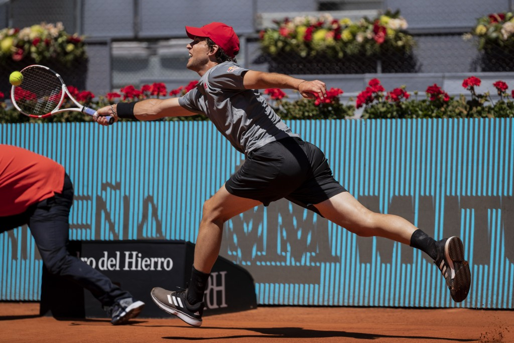 Austria's Dominic Thiem returns the ball to United States' John Isner during their match at the Mutua Madrid Open tennis tournament in Madrid, Spain, ...