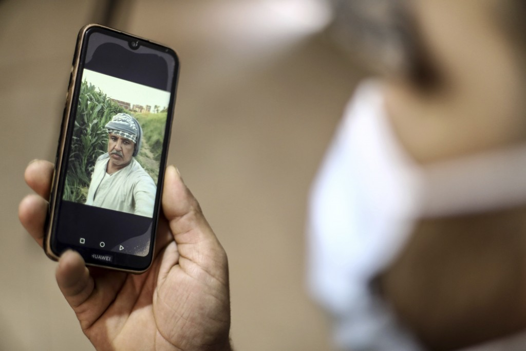 Amr Mahrous a relative of 50-year-old Ismail Abdallah looks at a photograph of him on his mobile phone in Egypt, Sunday, May 2, 2021. After two weeks ...
