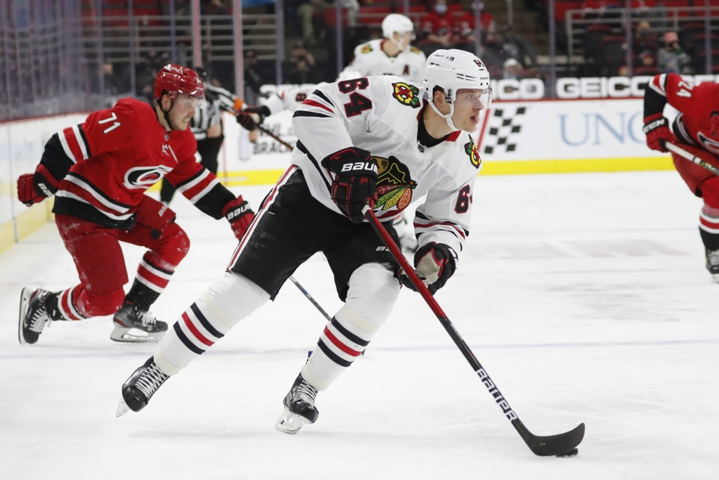 Chicago Blackhawks' David Kampf (64) drives the puck toward the net after making it past Carolina Hurricanes' Jesper Fast (71) during the first period...