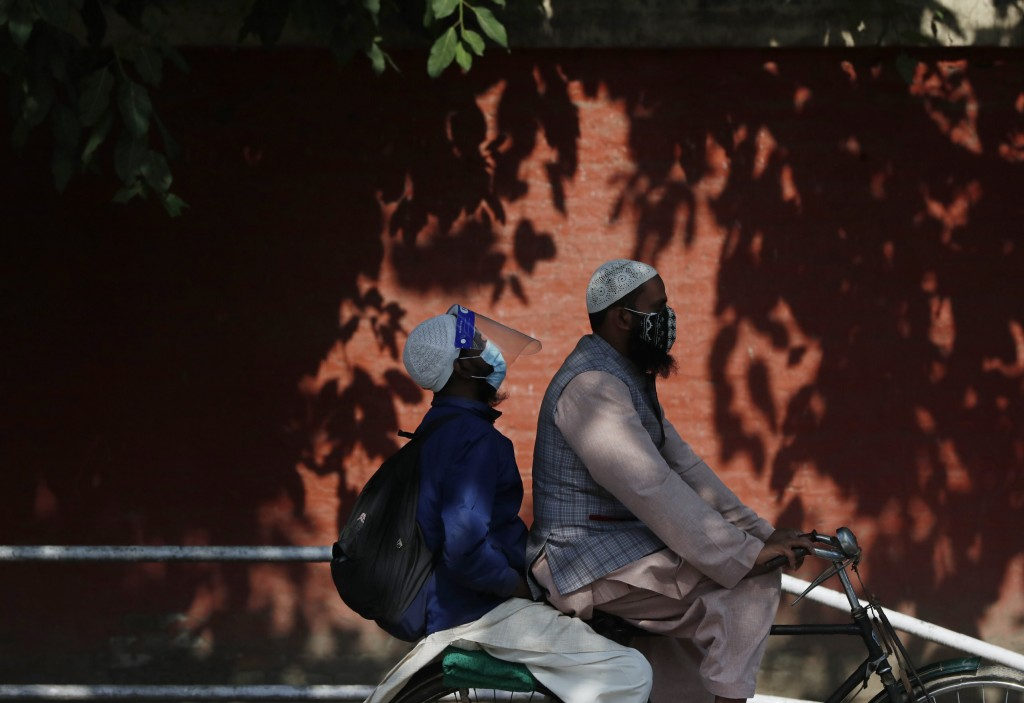 Nepalese men wearing face masks ride on a bicycle in Kathmandu, Nepal, Wednesday, May 5, 2021. Authorities extended lockdown in the capital Kathmandu ...