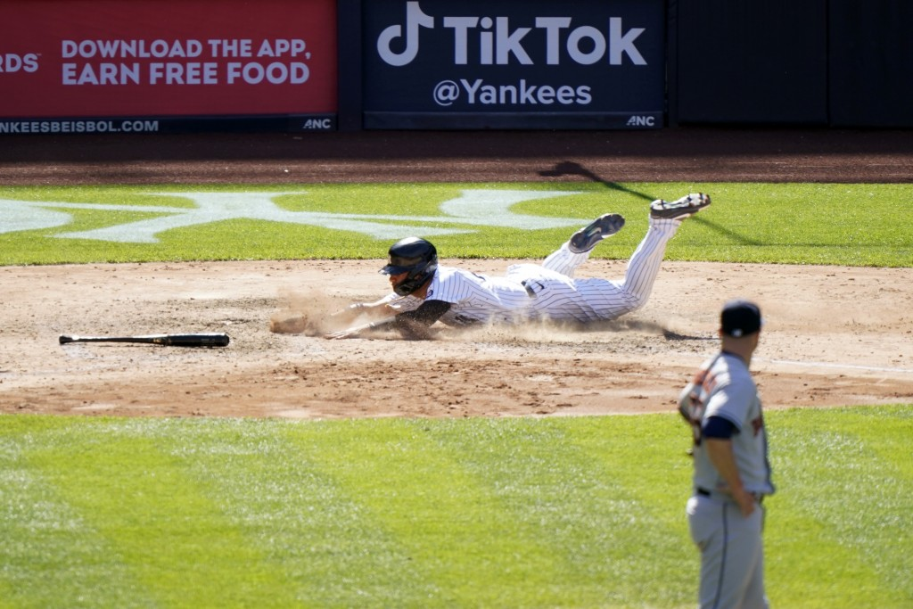 Houston Astros relief pitcher Ryan Pressly, foreground, watches as New York Yankees' Gleyber Torres scores on Aaron Hick's infield single during the e...