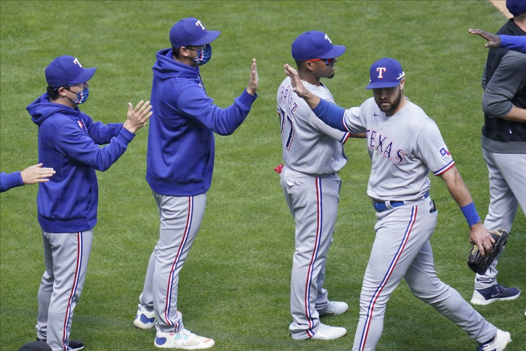 Texas Rangers' Joey Gallo, right, goes through the celebration line after making a diving catch of a ball off the bat of Minnesota Twins' Miguel Sano ...