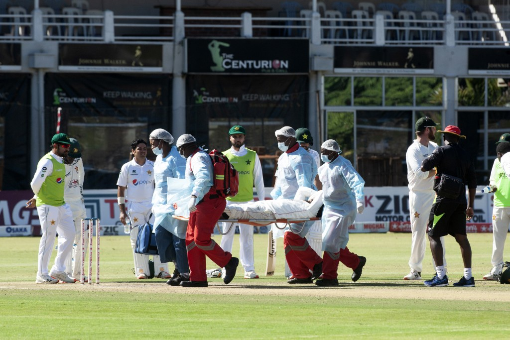 Medics carry Zimbabwean player Roy Kaia after he was injured during the second test cricket match against Pakistan at Harare Sports Club, Friday, May,...