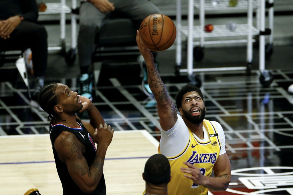 Los Angeles Lakers' Anthony Davis, right, goes up to basket next to Los Angeles Clippers' Kawhi Leonard, left, during the first half of an NBA basketb...