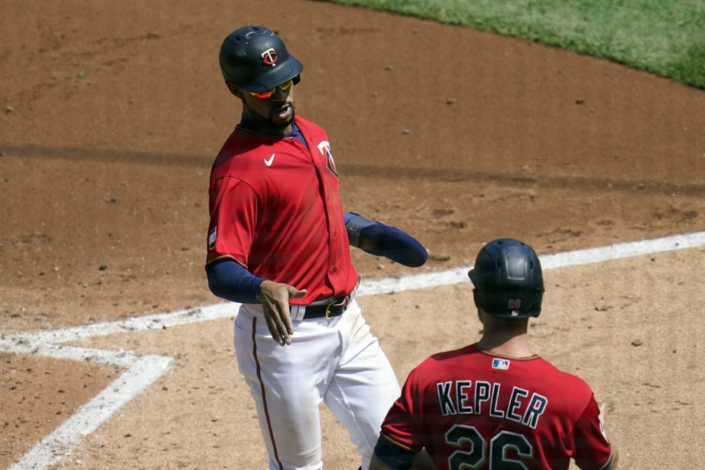 Minnesota Twins' Byron Buxton, left, scores on a two-run single by Minnesota Twins' Willians Astudillo in the third inning of a baseball game, Thursda...