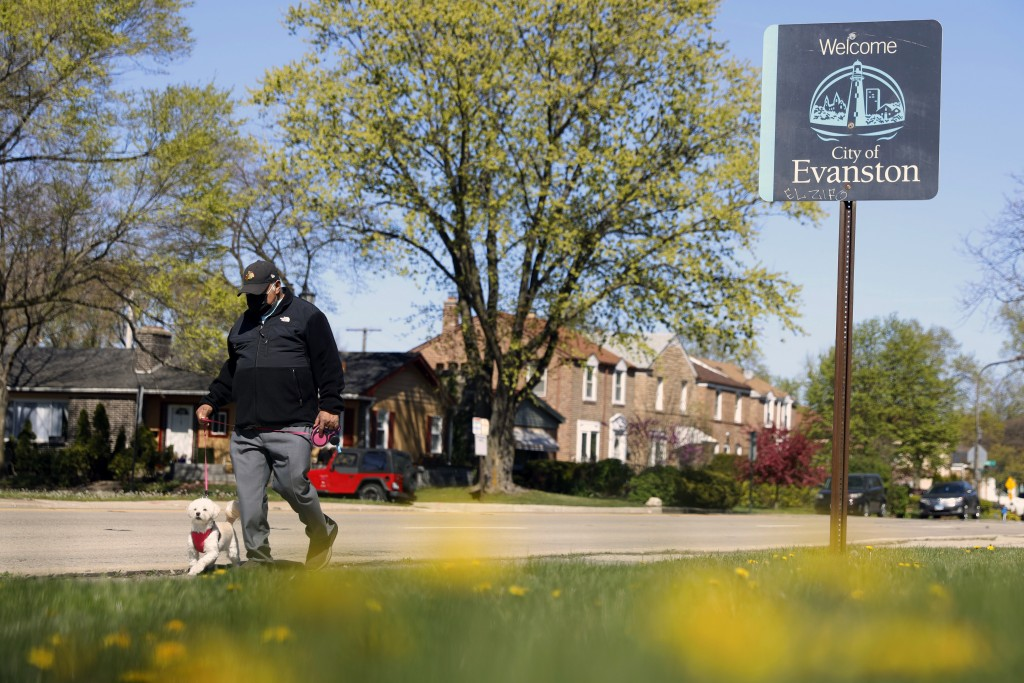 """A person walks a dog past a street sign reading """"Welcome to Evanston"""" in the predominantly Black 5th Ward in Evanston, Ill., Tuesday, May 4, 2021. The..."""