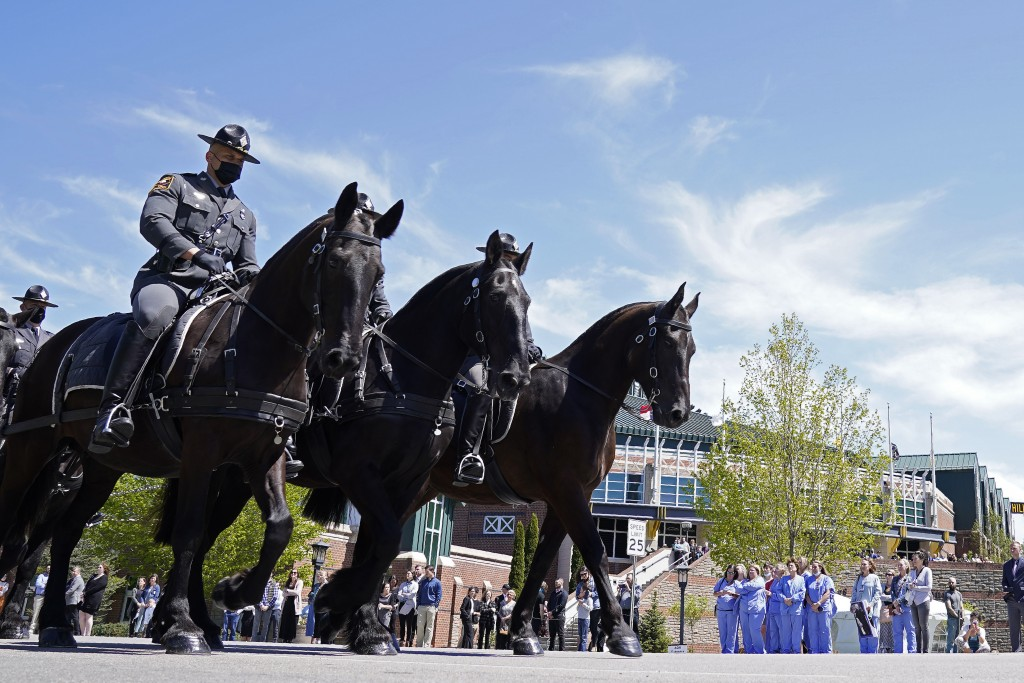 A processional passes the Holmes Convocational Center for the funeral services of Watauga County Sheriff's Deputies Sgt. Chris Ward and K-9 Deputy Log...