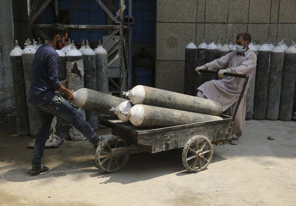 Workers load oxygen cylinders onto a hand cart to be carried inside the COVID-19 wards at a government run hospital in Jammu, India, Friday, May 7, 20...