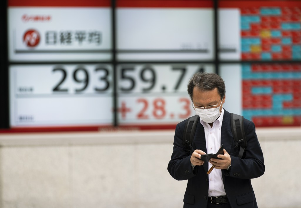 A man walks by monitors showing Japan's Nikkei 225 index at a securities firm in Tokyo on Friday, May 7, 2021. Asian shares rose Friday on optimism ab...