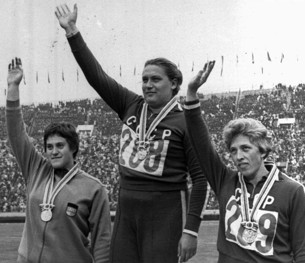 FILE - In this Oct. 20, 1964 file photo, Tamara Press, center, raises her hand on victory stand after winning the women's shot put finals with a new O...