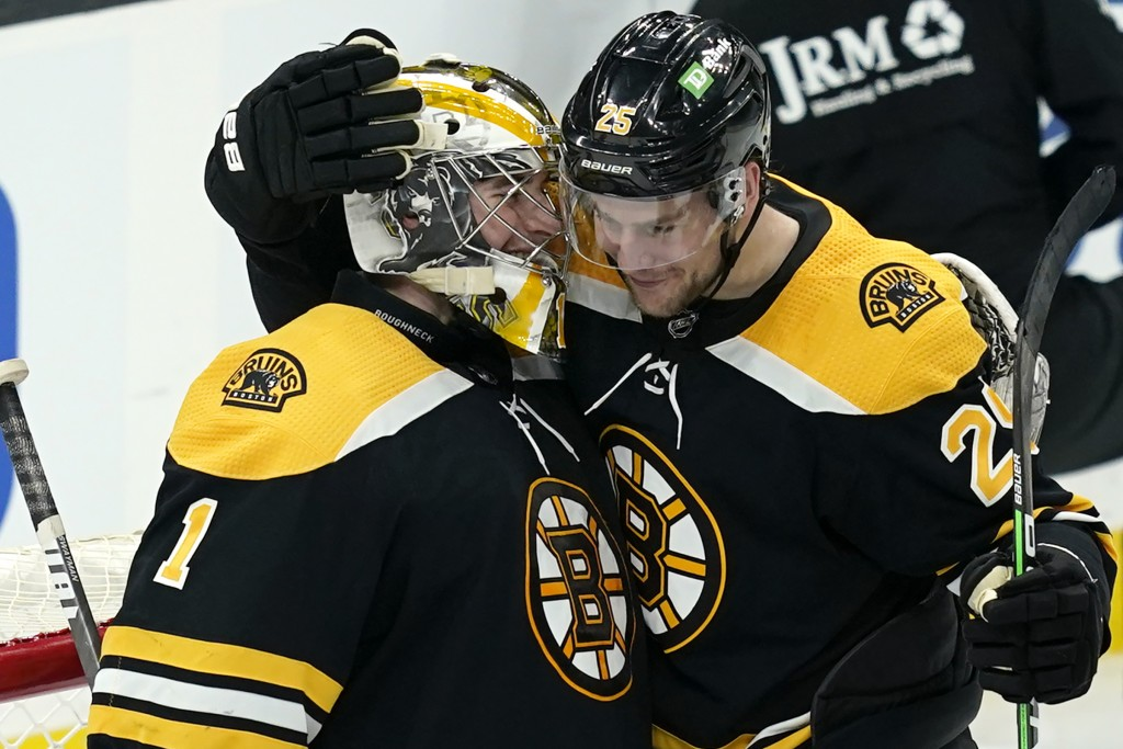 Boston Bruins goaltender Jeremy Swayman (1) and defenseman Brandon Carlo (25) celebrate their victory over the New York Rangers after an NHL hockey ga...