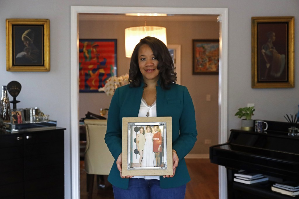 Robin Rue Simmons, alderwoman of Evanston's 5th Ward poses for a portrait holding a photograph of her mother, aunt and grandmother in her home in Evan...