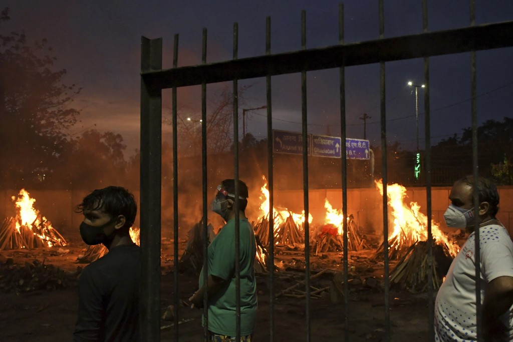 People watch burning funeral pyres of their relatives who died of COVID-19 in a ground that has been converted into a crematorium in New Delhi, India,...