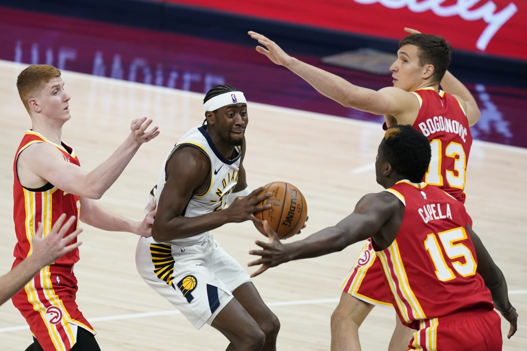 Indiana Pacers' Caris LeVert (22) looks for a shot between Atlanta Hawks' Bogdan Bogdanovic (13), Clint Capela (15) and Kevin Huerter during the secon...