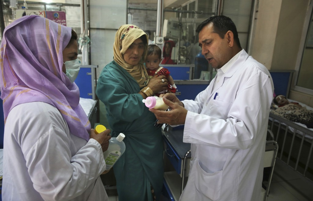 FILE - In this Aug. 21, 2019 file photo, a doctor briefs the mother of a malnourished child on how to feed her baby in a ward at Indira Gandhi hospita...