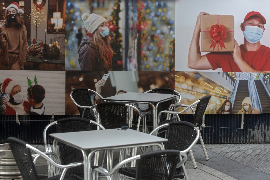 FILE - In this Thursday, Dec. 17, 2020 file photo, empty tables and chairs in a terrace bar sit by posters of people wearing face masks in Madrid, Spa...