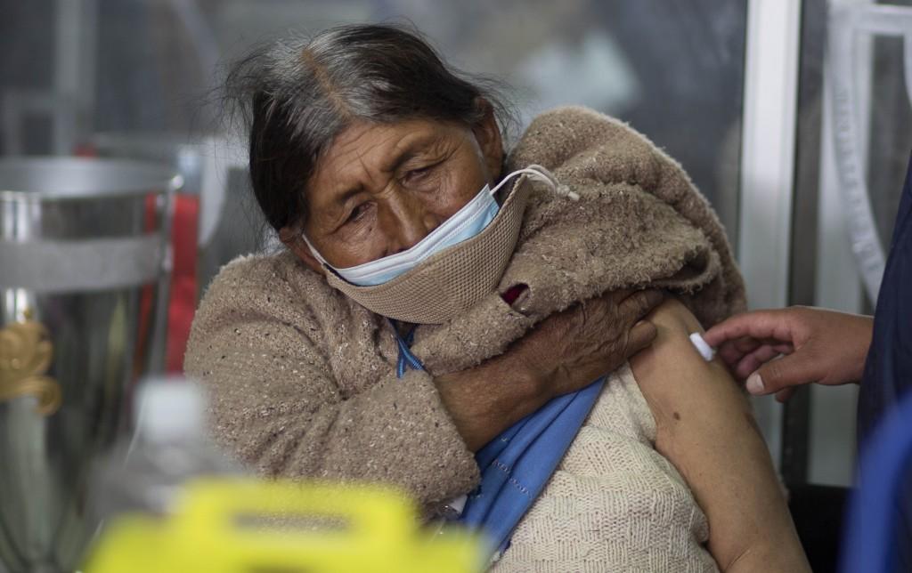A woman sits for a few minutes after getting a shot of the Sputnik V COVID-19 vaccine at the Universidad Publica de El Alto, during a vaccination driv...