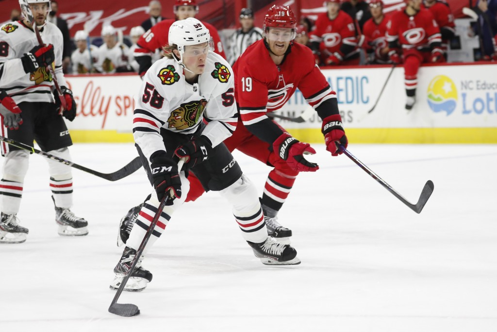 Chicago Blackhawks' MacKenzie Entwistle (58) moves the puck past Carolina Hurricanes' Dougie Hamilton (19) during the first period of an NHL hockey ga...