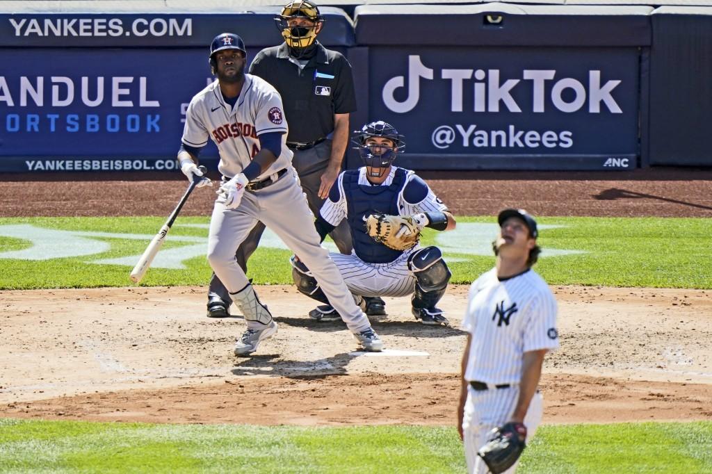 Houston Astros designated hitter Yordan Alvarez (44) and New York Yankees starting pitcher Gerrit Cole (45) watch Alvarez's solo home run in the seven...