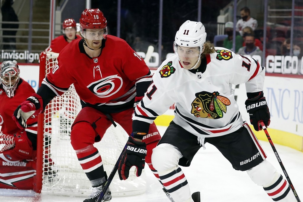 Chicago Blackhawks' Adam Gaudette (11) drives the puck around Carolina Hurricanes' Dougie Hamilton (19) during the first period of an NHL hockey game ...