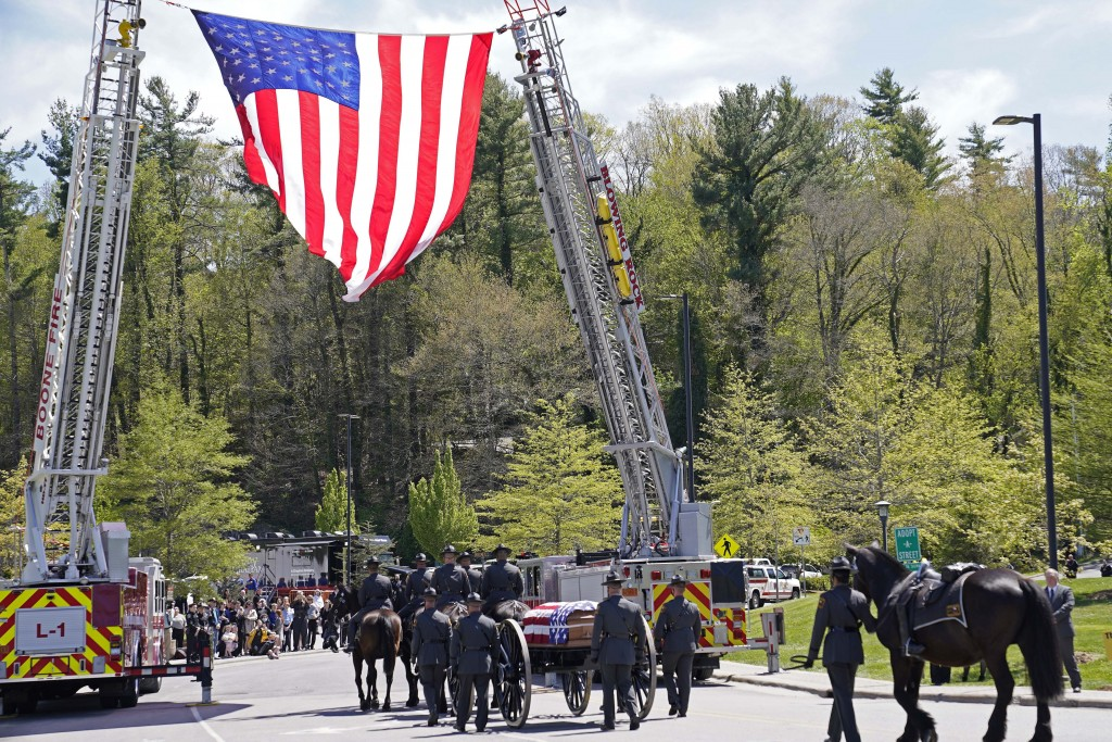A processional approaches the Holmes Convocational Center for the funeral services of Watauga County Sheriff's Deputies Sgt. Chris Ward and K-9 Deputy...