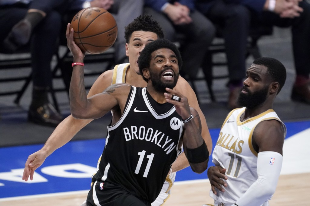 Brooklyn Nets guard Kyrie Irving (11) drives to the basket for a shot past Dallas Mavericks guard Josh Green, rear, and Tim Hardaway Jr., right, in th...