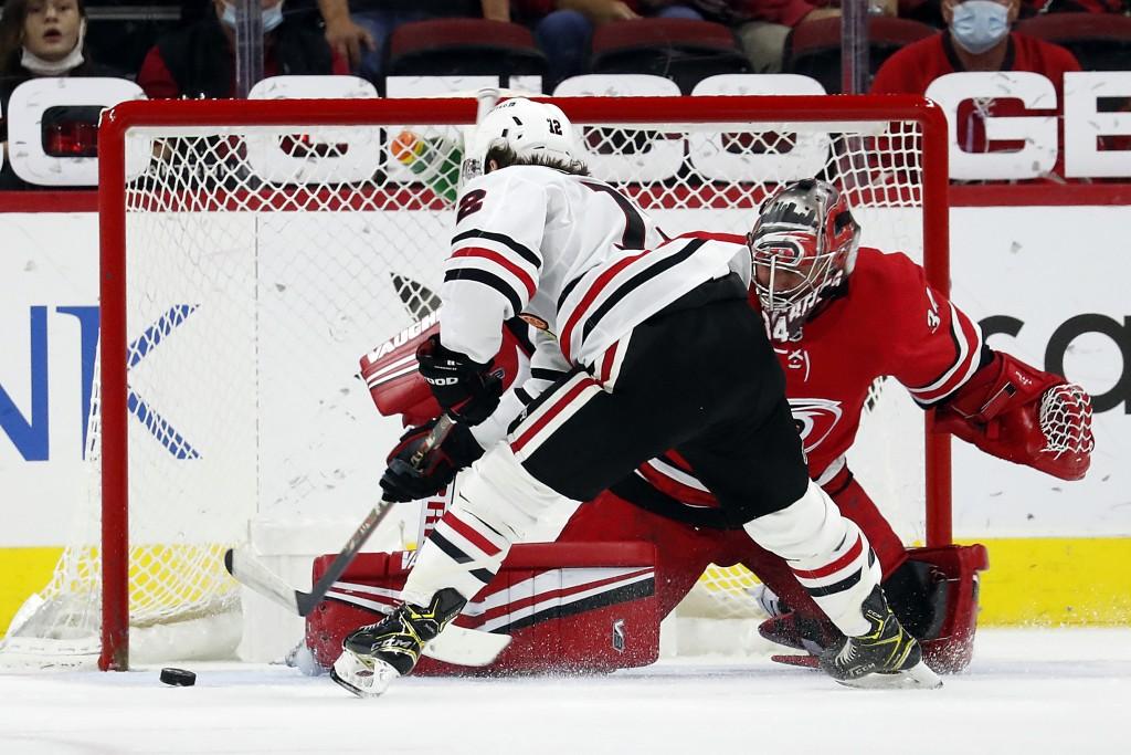 Carolina Hurricanes goaltender Petr Mrazek (34) blocks the shot of Chicago Blackhawks' Alex DeBrincat (12) during the second period of an NHL hockey g...