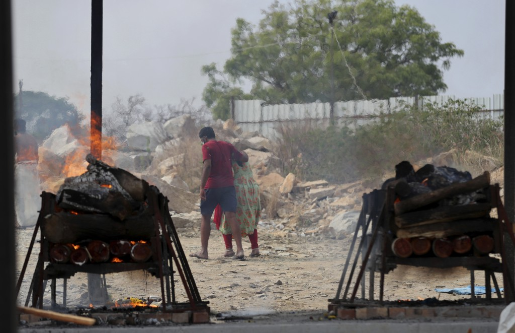 Family members of COVID-19 victims leave as their funeral pyres burn at an open crematorium set up at a granite quarry on the outskirts of Bengaluru, ...
