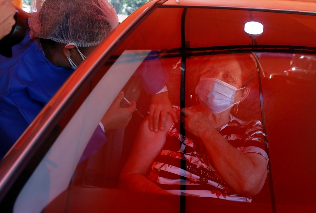 An elderly woman gets a shot of the AstraZeneca vaccine for COVID-19 from a car under a red tarp set up outside Trinidad Maternity Hospital in Asuncio...