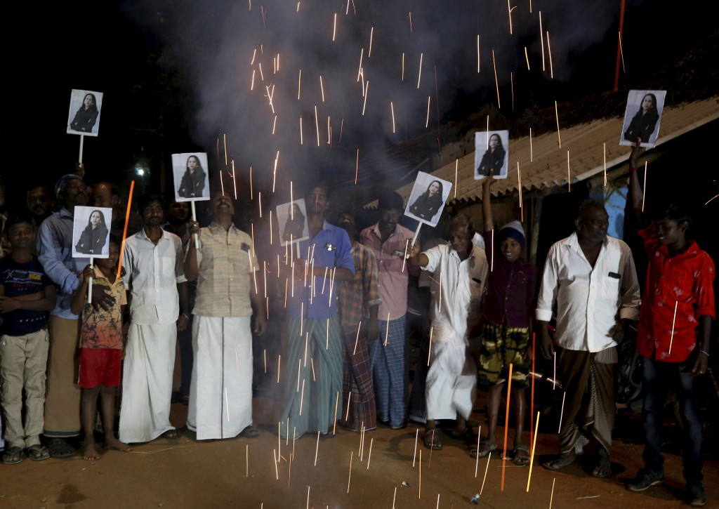 FILE - In this Jan. 20, 2021, file photo, villagers release firecrackers and hold placards featuring Vice President Kamala Harris after her inaugurati...