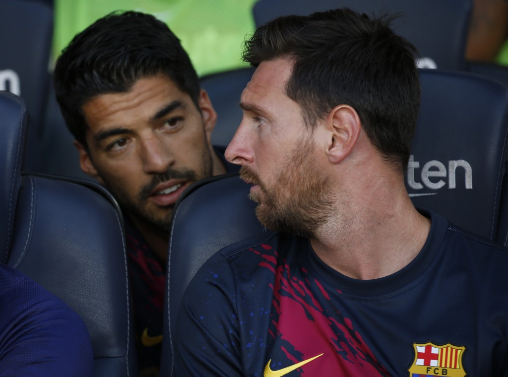 FILE - In this Sunday, Aug. 4, 2019 file photo, Barcelona's Lionel Messi, right, talks with teammate Luis Suarez on the bench before the Joan Gamper t...