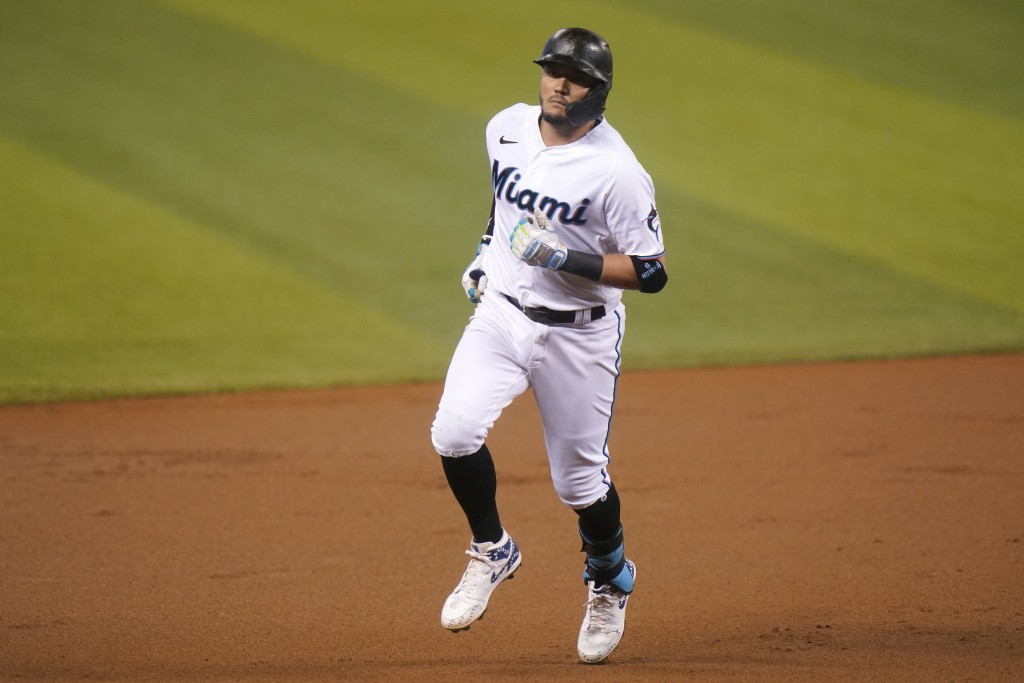 Miami Marlins' Miguel Rojas rounds the bases after hitting a solo home run during the first inning of a baseball game against the Arizona Diamondbacks...