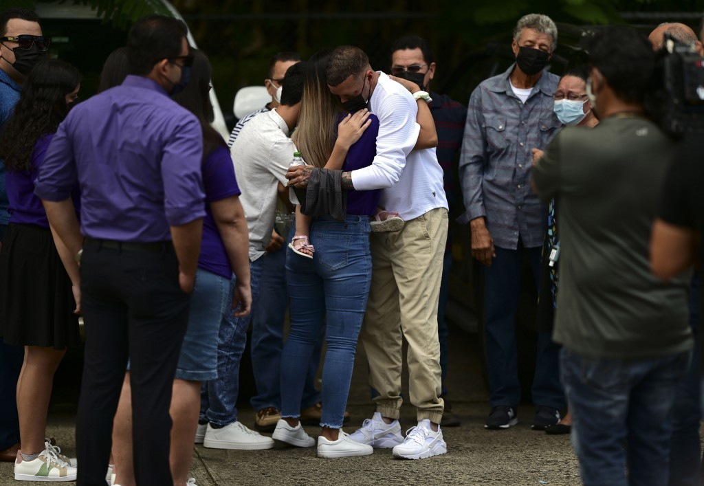 Jose Antonio Rodriguez, center right, is embraced as he arrives at a wake for his 27-year-old-daughter Keishla Rodriguez, whose lifeless body was foun...