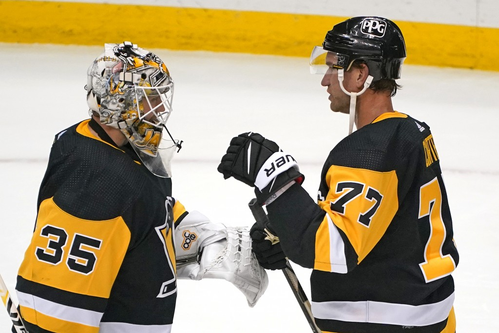 Pittsburgh Penguins center Jeff Carter (77) celebrates with goaltender Tristan Jarry after a win over the Buffalo Sabres in an NHL hockey game in Pitt...