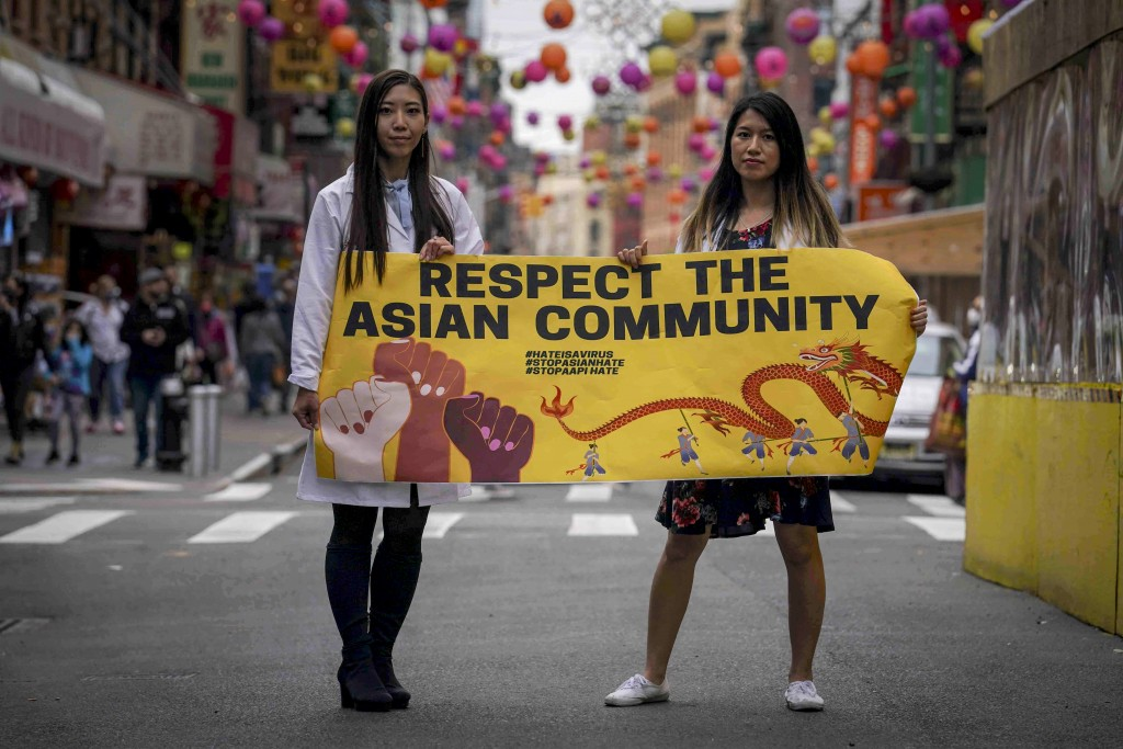 Dr. Michelle Lee, left, a radiology resident, and Ida Chen, right, a physician assistant student, unfold a banner Lee created to display at rallies pr...